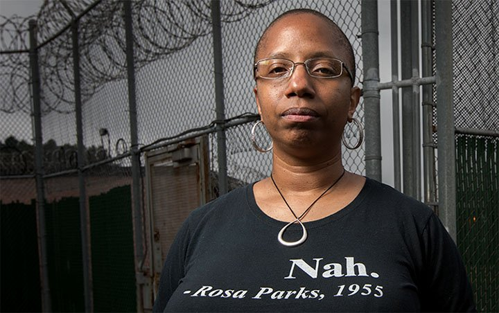 Erin Corbett stands outside a prison wearing a t-shirt promoting civil rights. (Photo/Swarthmore College)