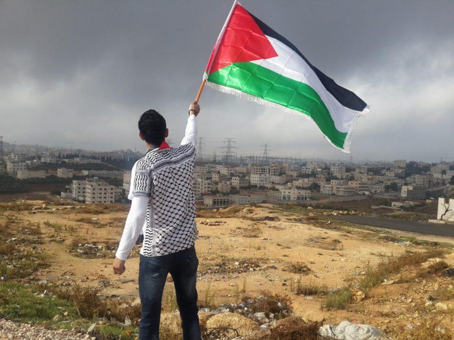 A+man+waves+the+Palestinian+flag+over+Palestine.+%28Photo%2FAhmed+Abu+Hameeda%2FUnsplash