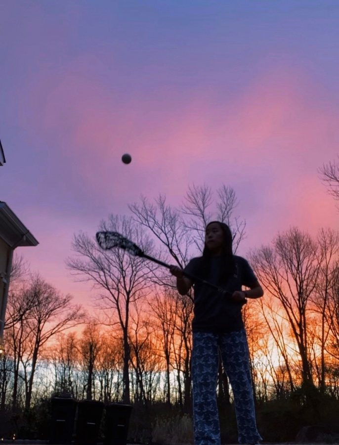 (Photo/Madeline Chia) Madeline Chia '21 playing  lacrosse outside during quarantine.