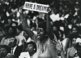 A protestor stands up for her rights holding a sign quoting MartIn Luther King Jr. (Photo/National Museum of American History)