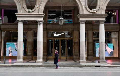 A woman wearing a respiratory mask walks past a closed Nike shop (Photo/Nicolò Campo/ WGN9)